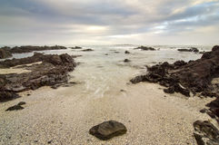 Rocky beach and clouds Stock Photography