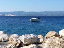 Rocky beach in Croatia with a boat in background. Wild croatian beach with rocks Royalty Free Stock Image