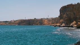 Rocky Beach em Egito Praia em uma ba?a no litoral com as ondas no mar e nos recifes de corais azuis filme
