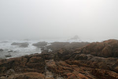 Rocky beach in a foggy afternoon Stock Images
