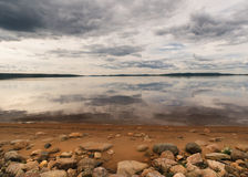 Rocky beach fronts lake reflecting dramatic skies in Finnish Lapland. Royalty Free Stock Photo