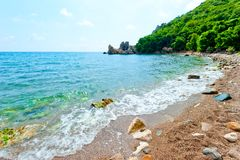 Rocky beach, green hill. Azure waters of the sea Royalty Free Stock Images