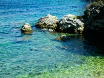 Rocky beach and green water. Clear azur, turquoise water. Environment Stock Images