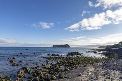 Rocky beach and Islet. A rocky beach looking out at the Islet of Vila Franca do Campo stock image