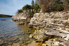 Rocky beach at Kassiopi village in Corfu, Greece.  stock photos
