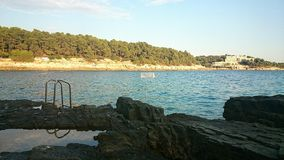 Rocky beach. With ladder and waterpolo goal in the sea Stock Photo