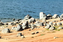 Rocky beach on the Lake Jindabyne foreshore. Rocky beach on the foreshore of Lake Jindabyne, featured in the background Royalty Free Stock Photo
