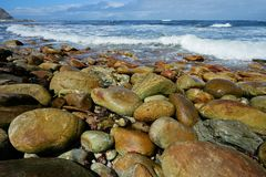 Rocky beach with waves. Rocky beach with large smooth pebbles and waves on a sunny morning royalty free stock images