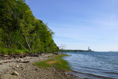 Rocky beach lined with trees on Cousins Island with Large Gas Po Royalty Free Stock Images