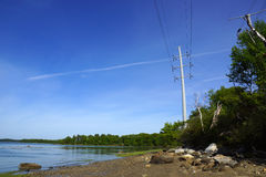 Rocky beach lined with trees on Cousins Island with Large Power. Line overhead, Maine, USA Stock Photos