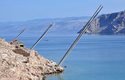 Rocky beach in Lukovo bay with fishing platforms, Croatia Stock Photos