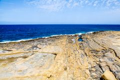 Amazing rocky beach in Sliema, Malta on a sunny day. Rocky beach in Malta with amazing sky on a sunny day Royalty Free Stock Images