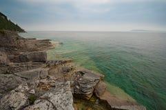 Rocky Beach med blått vatten Fotografering för Bildbyråer