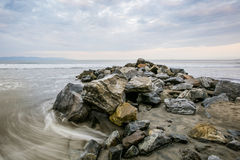 Rocks and Sea. Rocky beach at morning with a cloudy sky Royalty Free Stock Image