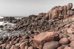 Rocky Beach Ocean Coastline Vintage. Rocky beach shoreline along ocean waves coastline landscape in vintage photo tones Royalty Free Stock Images