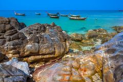 Rocky beach with parked boats. Stones on Lanta. Krabi, Thailand stock images