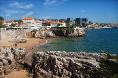 Rocky beach with people and villas. And houses in the background royalty free stock images