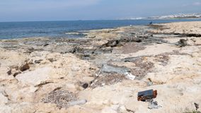 Rocky beach polluted with plastic bottles and trash. Fisherman and ship on the background.  stock footage