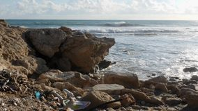 Rocky beach polluted with plastic bottles and trash. Waste and recycle concept. Slow motion.  stock video footage
