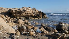 Rocky beach polluted with plastic bottles. Waves hitting the sandy beach with plastic bottles. Slow motion.  stock footage