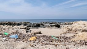 Rocky beach polluted with plastic and garbage. Waste and recycle concept. Rocky beach polluted with plastic and garbage. Waste and recycle concept stock video footage