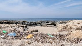Rocky beach polluted with plastic and garbage. Waste and recycle concept. Slow motion.  stock footage
