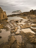 Rocky Beach with Pools. Rocky beach with some little pools on the foreground and a mountain on the background Royalty Free Stock Image