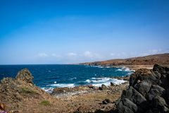 Rocky beach on the Rugged costal landscape on Aruba`s north coast. Dry land and ocean meet in the beautiful landscape on the North coast of Aruba. Wind turbines stock images