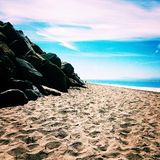 Rocky beach. Sand rocks ocean and sky all blending together to form the beautiful west coast in Santa Cruz California Royalty Free Stock Image