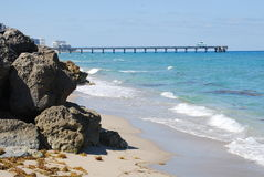 Rocky beach by sea. Scenic view of rocky beach by blue sea with long pier in background, Florida, U.S.A Stock Photography