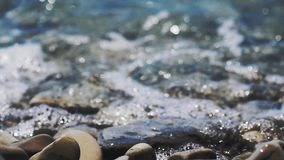 A rocky beach by the sea, waves of sea on a sunny day. Pure waves moving on multi colored polished stones and pebbles