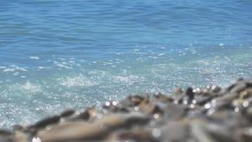 A rocky beach by the sea, waves of sea on a sunny day. slow motion. 1920x1080. Hd stock footage