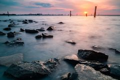 Dramatic view of the rocky beach in Selangor during sunset stock photography