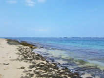 Rocky beach with Shallow wavy ocean waters of Camp Mokuleia Beach. Looking into the pacific ocean with a clear blue sky on Oahu stock photography