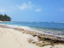 Rocky beach with Shallow wavy ocean waters of Camp Mokuleia Beach. Looking into the pacific ocean with a clear blue sky on Oahu stock image