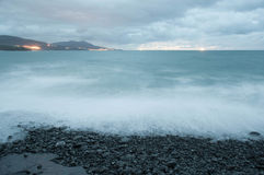 Rocky beach shore in a stormy sunset Royalty Free Stock Image