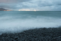 Rocky beach shore in a stormy sunset Stock Images