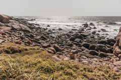 Rocky Beach Ocean Summer Coastline Vintage. Rocky beach shoreline summer along ocean waves coastline landscape in vintage photo tones Stock Photography
