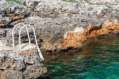 A rocky beach with a staircase to the sea. Royalty Free Stock Photography