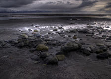 Rocky beach with storm cloud Royalty Free Stock Images