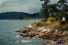 Rocky  beach in the Strait of Georgia. Rocky beach in the Strait of Georgia, British Columbia, the coastline and the coastal village on the opposite shore of the royalty free stock photos