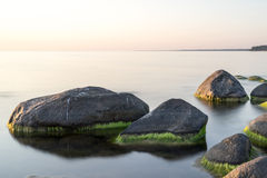 Rocky beach at sunset with milky water Stock Image