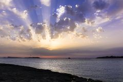 Rocky Beach at Sunset. Or sunrise  with Sunrays on Cloudy sky Royalty Free Stock Image