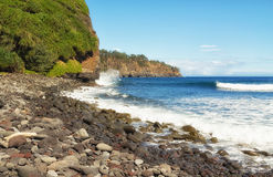 Rocky beach, surf, and cliffs of Hawaii. Surf crashes into rocky shore and cliffs of Kohala, eroding cliffs. Cliffsalong the  north coast of the Big Island of Royalty Free Stock Photos