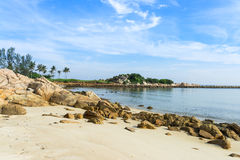 Rocky Beach. Tropical rocky beach with golf course at the background royalty free stock image
