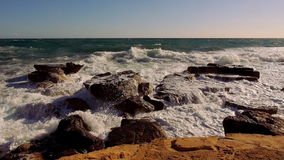 Rocky beach with turbulent water and breaking ocean waves stock video
