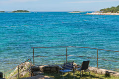 Rocky beach with two chairs in Istria Stock Photography