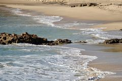 Rocky beach with waves. Rocky beach showing sand and rugged terrain with waves rolling on the shore royalty free stock photography