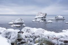 Evening light and icy weather on shore like fairy tale country. Rocky beach on wintertime. Evening light and icy weather on shore like fairy tale country Royalty Free Stock Images