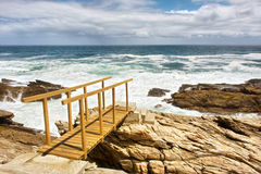 Rocky beach and wooden bridge Stock Photo